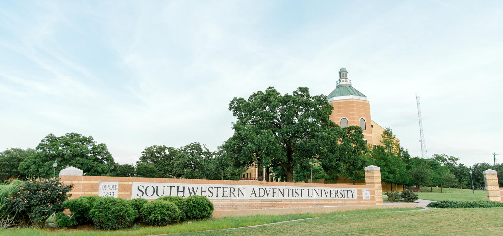 """Campus sign made of bricks that reads """"Southwestern Adventist University"""" with the top of Pechero Hall showing behind trees"""