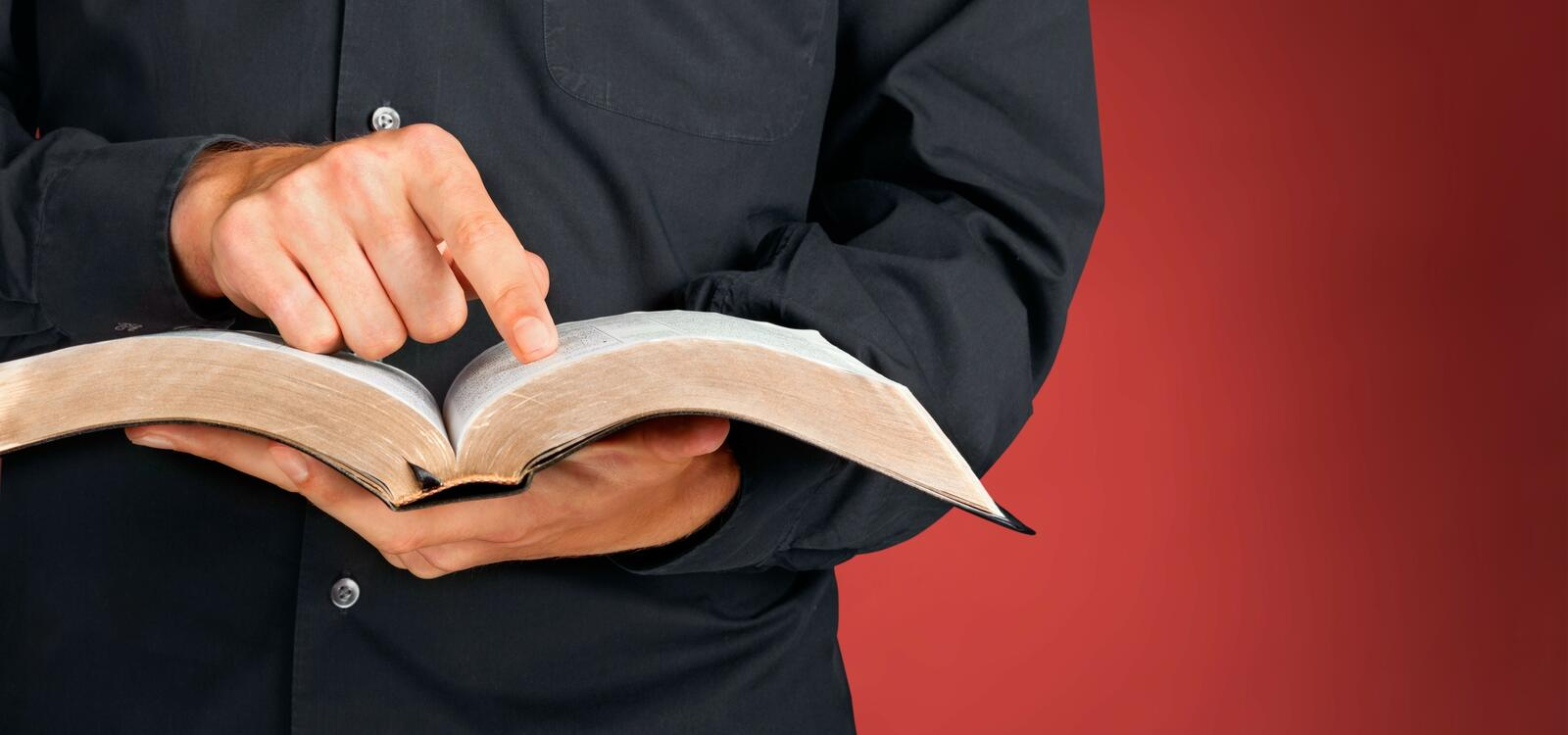 Cropped photo of a man, wearing a black button-up, holding an open bible while pointing to a verse