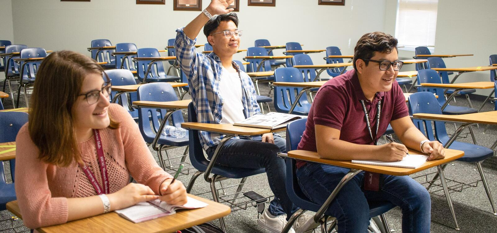 Three students sitting in a classroom facing the front as the listen attentively and take notes. One student is raising his hand to ask a question.