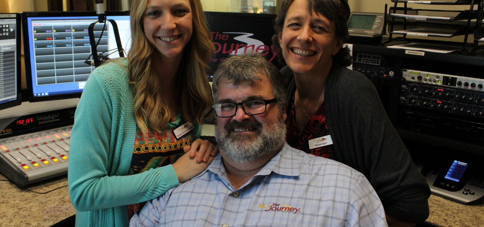 Danae Songy and Wanda Agee posing behind Mike Agee inside the radio station