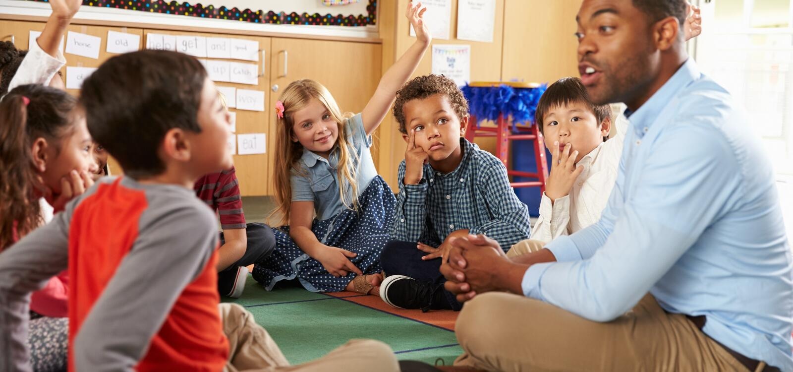 Sitting among his students, a teach sits on the floor with his legs crossed as he talks to children with their hands raised