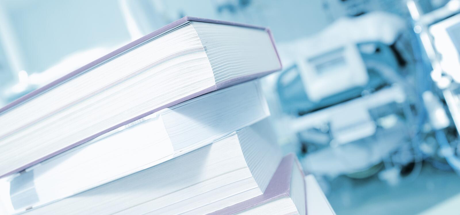 In front of a blue background, a stack of four textbooks sits on a white table