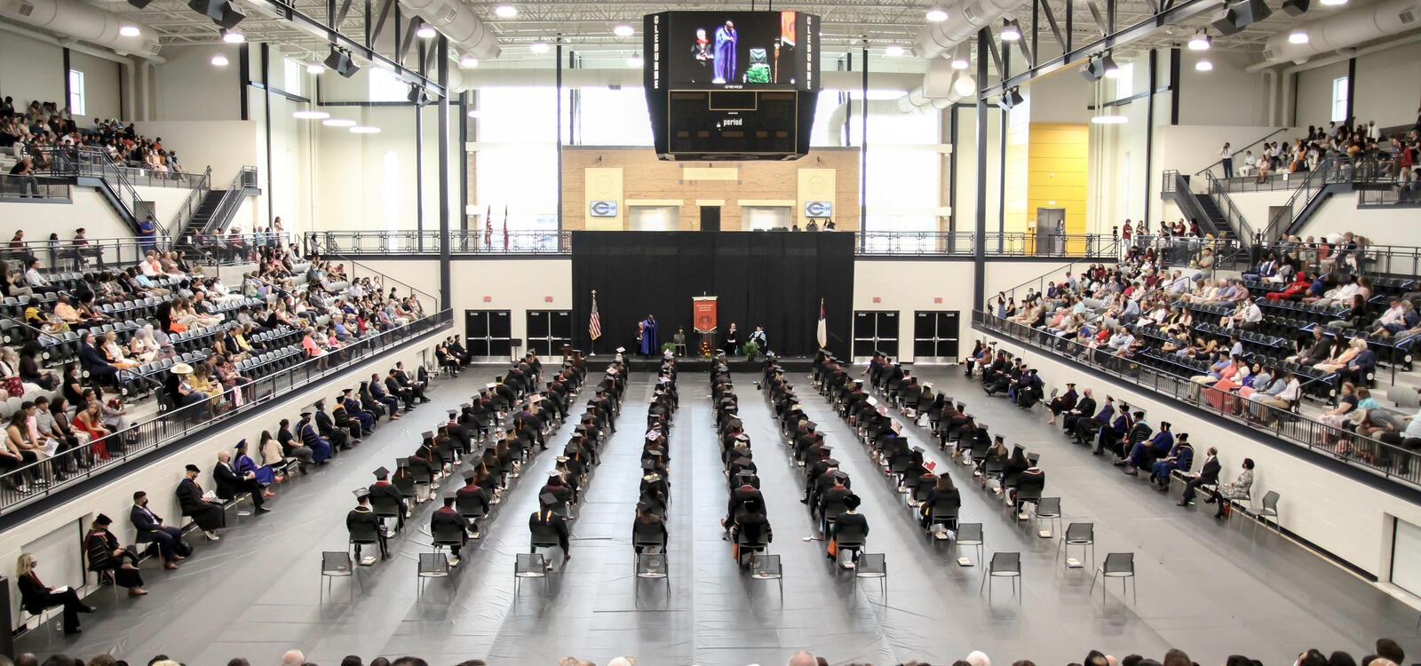 Graduates sitting in rows in a large stadium with guests to the right, left, and back and the stage to the front
