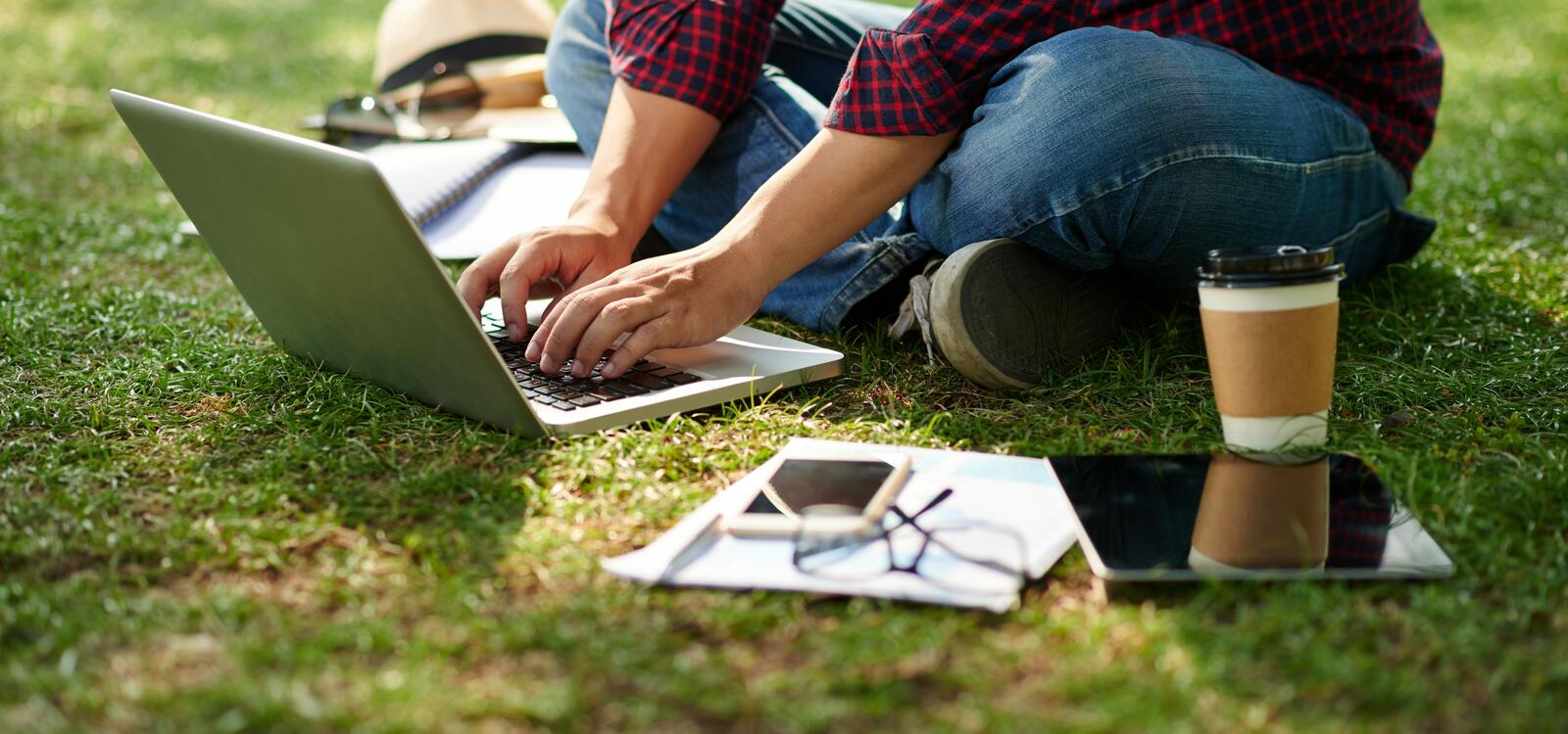 Sitting on the grass, a student types on his laptop as his coffee, tablet, notebooks and phone surround him