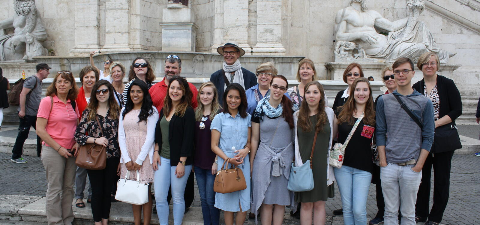 Students from the Honors Program smile as they stand in front of statues of greek mythology