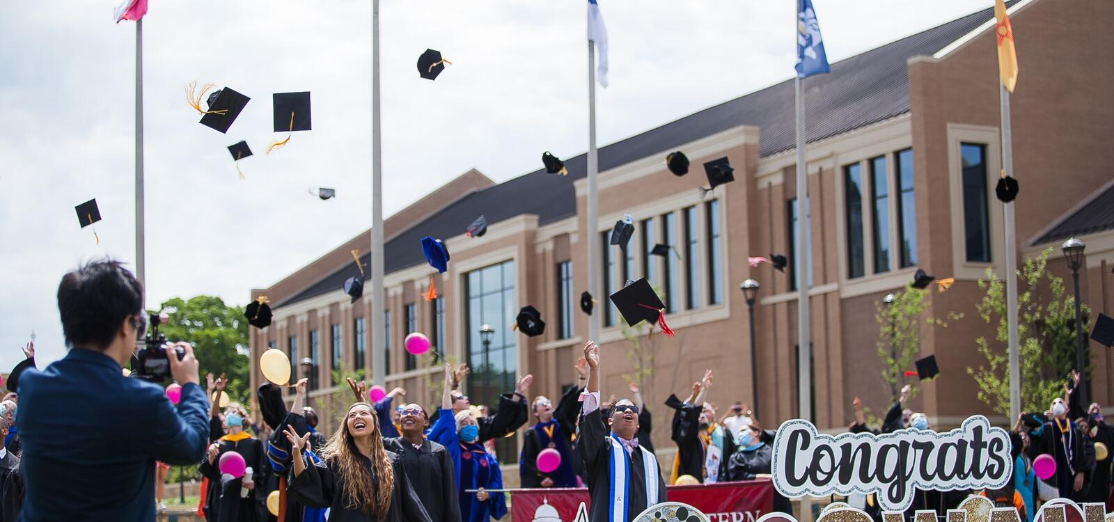 Graduating seniors throw their caps in the air while being surrounded by proud faculty and staff