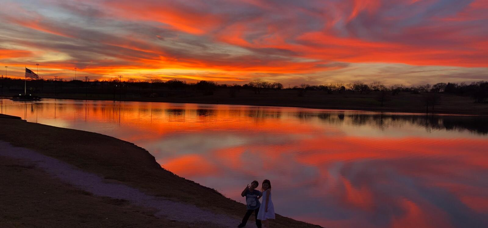The sunset sets in pink, orange and blue colors and reflects off of the water of the duck pond