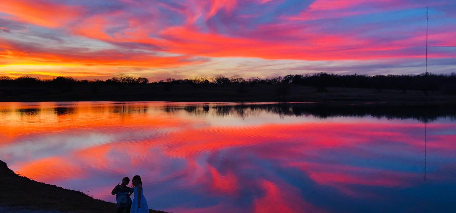 A beautiful sunset made up of blues, pinks, oranges and yellows reflect off of the pond's water
