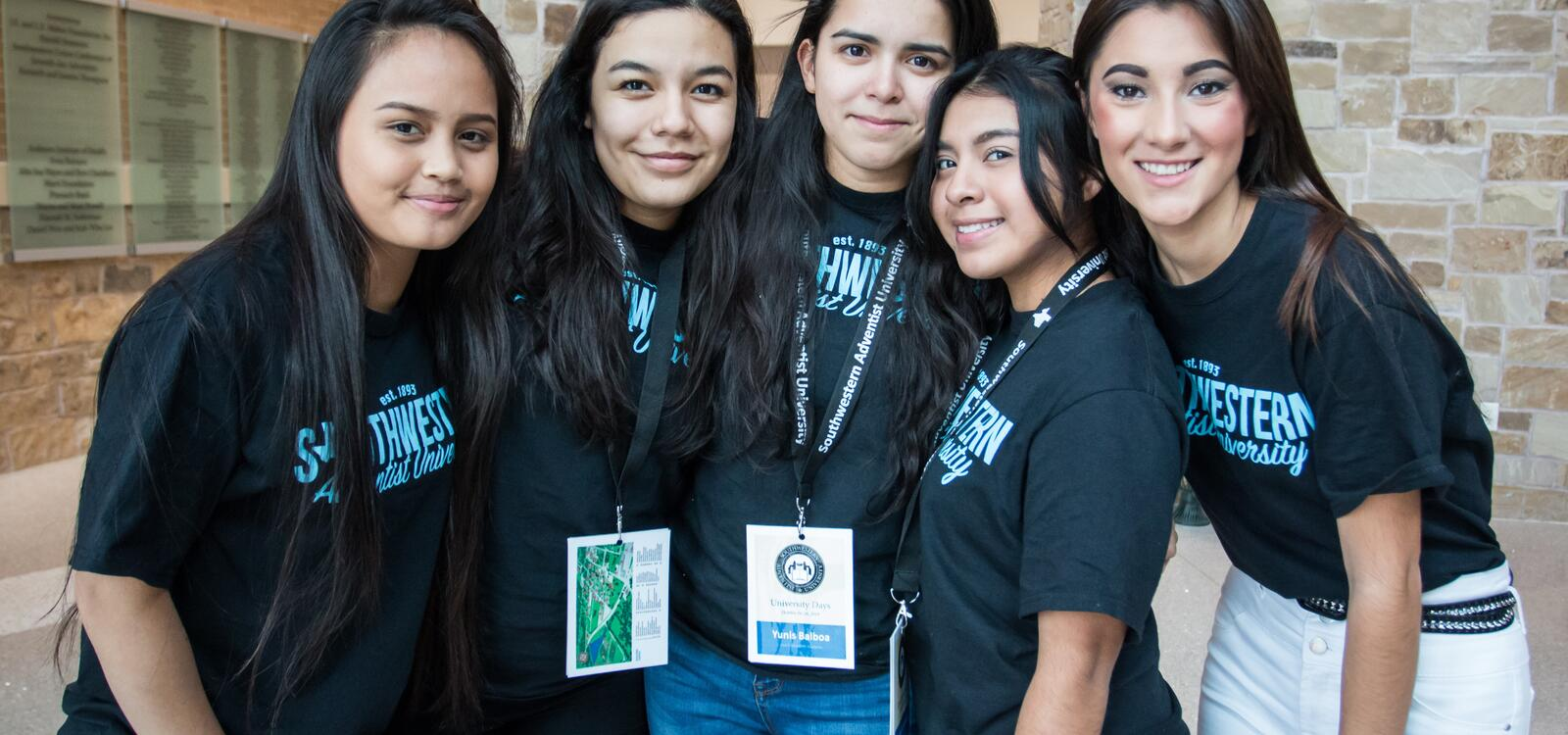 A group of five high school senior girls wearing black t-shirts with a blue Southwestern logo hugging eachother as they smile for a photo