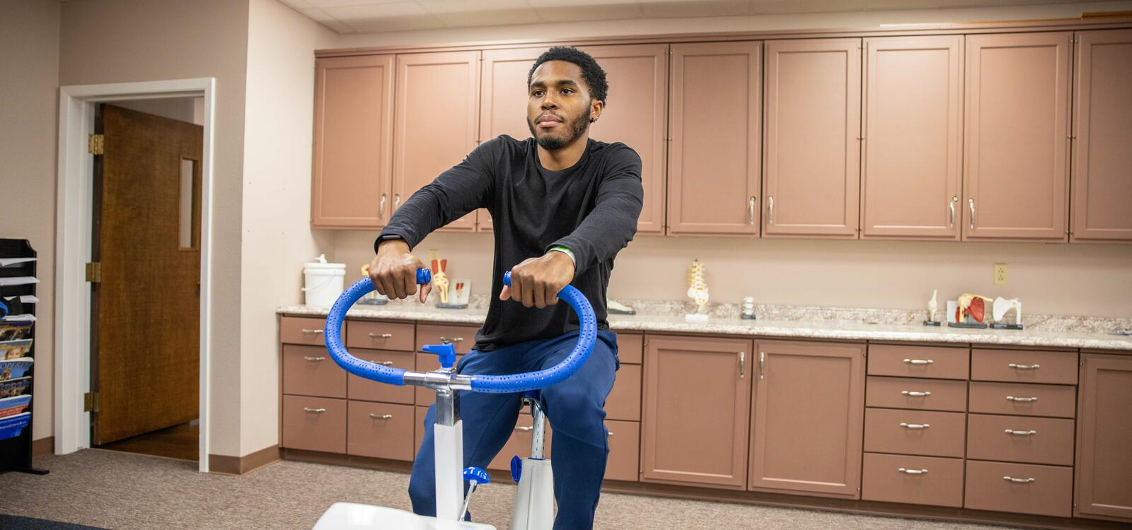 Student using exercise machine in kinesiology building.