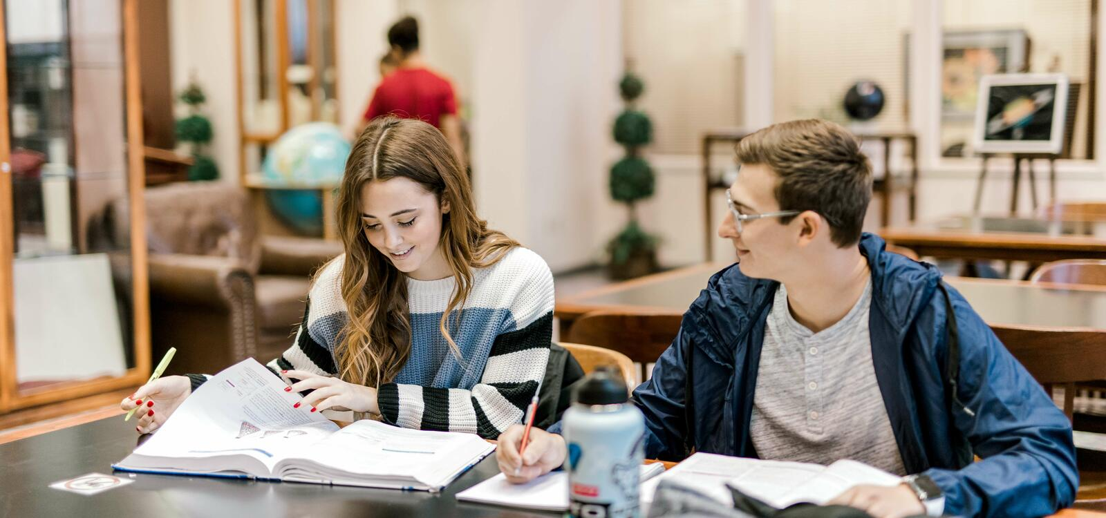 Two students sit at a rectangular table and flip through their textbooks