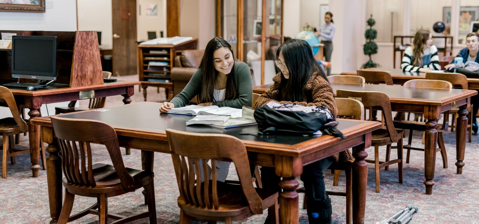 Two female students smiling as the sit at a table at the library and read through a textbook
