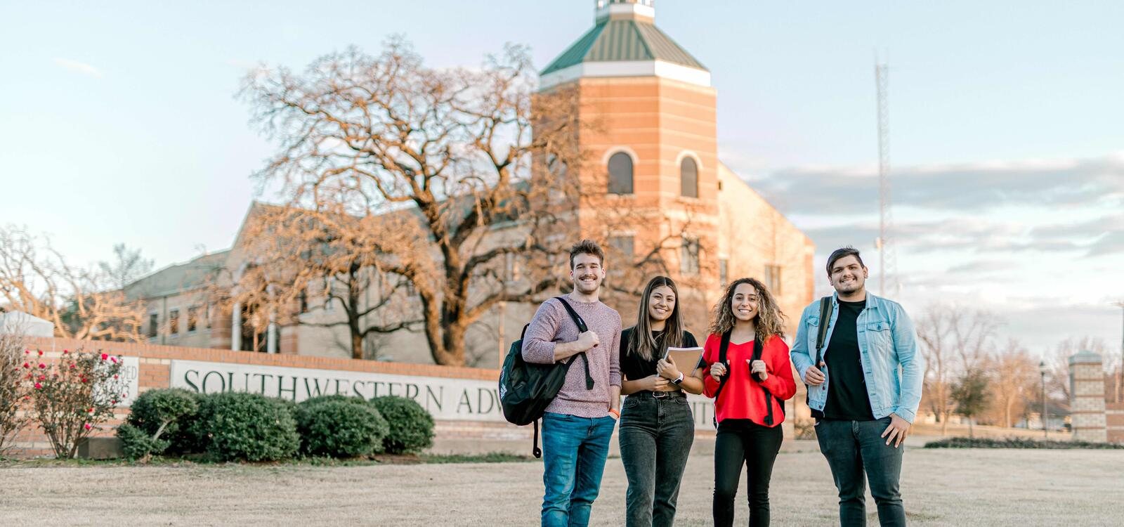 """Four students, with backpacks, smile together as they stand in front of a bricked sign that reads """" Southwestern Adventist University"""""""