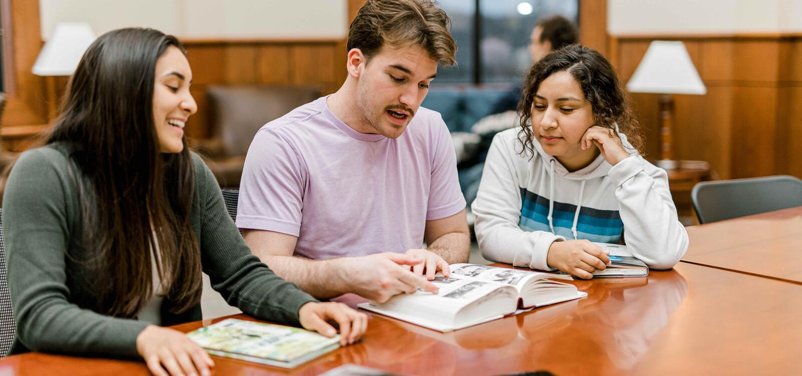 Three students look at a book as they sit at a rectangular table in the pechero student lounge