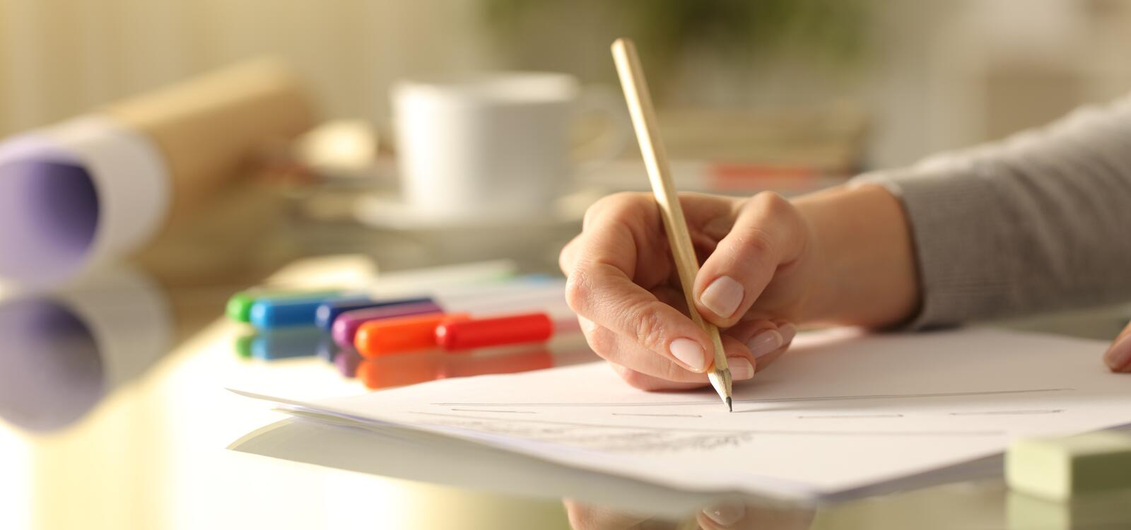 A woman uses a pencil to draw and take notes on a white paper
