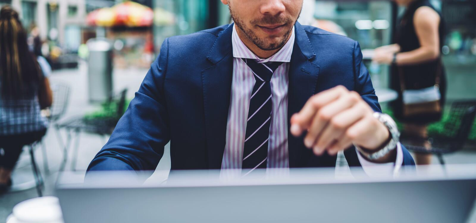 A man sits in front of a laptop with a navy blue sui, striped lavender shirt and a navy blue tie to match
