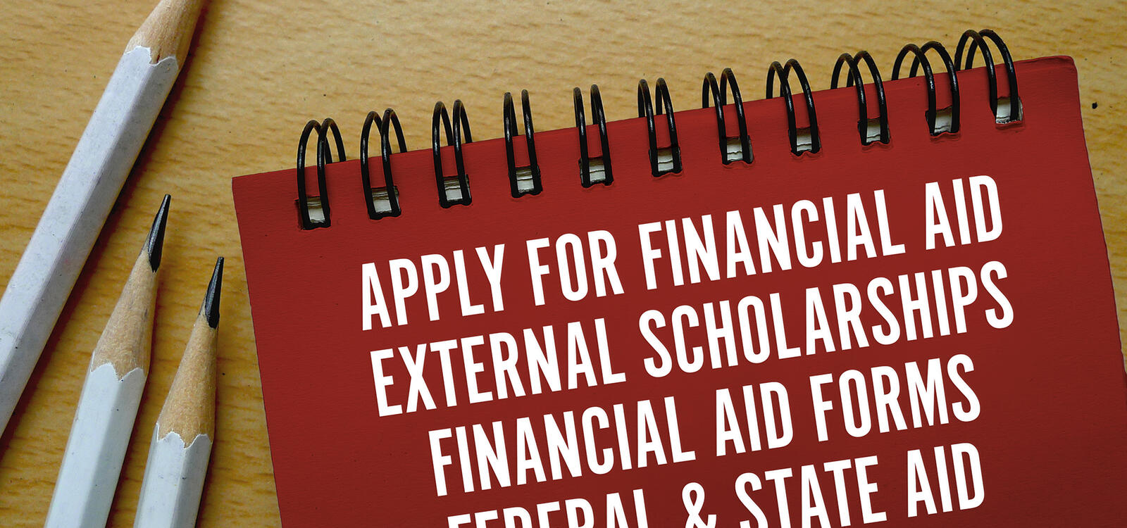 On a red notebook is a note encouraging students to apply for financial aid, external scholarships and more.