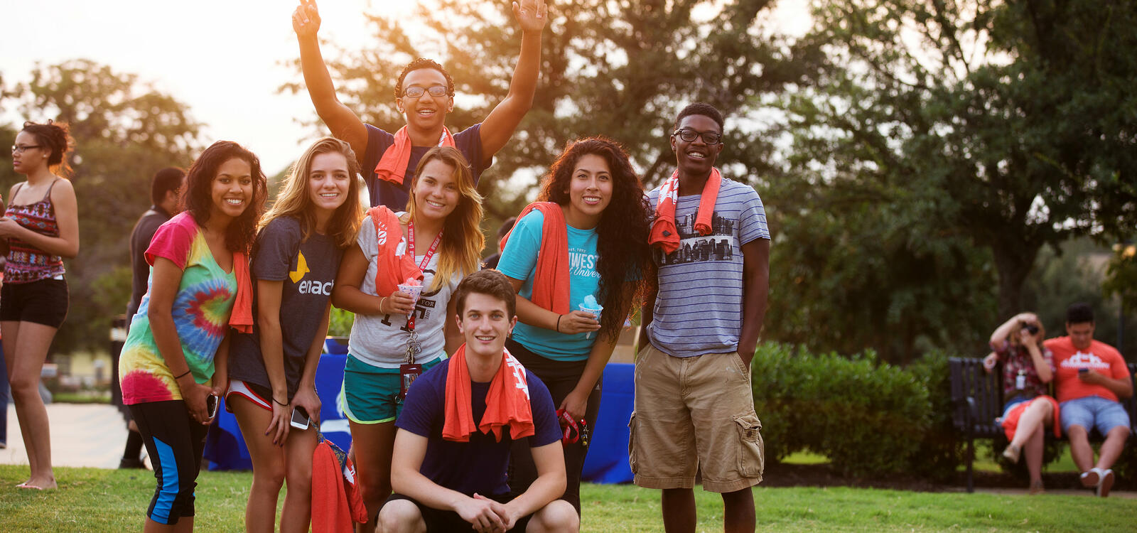 A group of seven students wearing summer clothing, smile in a group as they all have orange t-shirts arund their necks