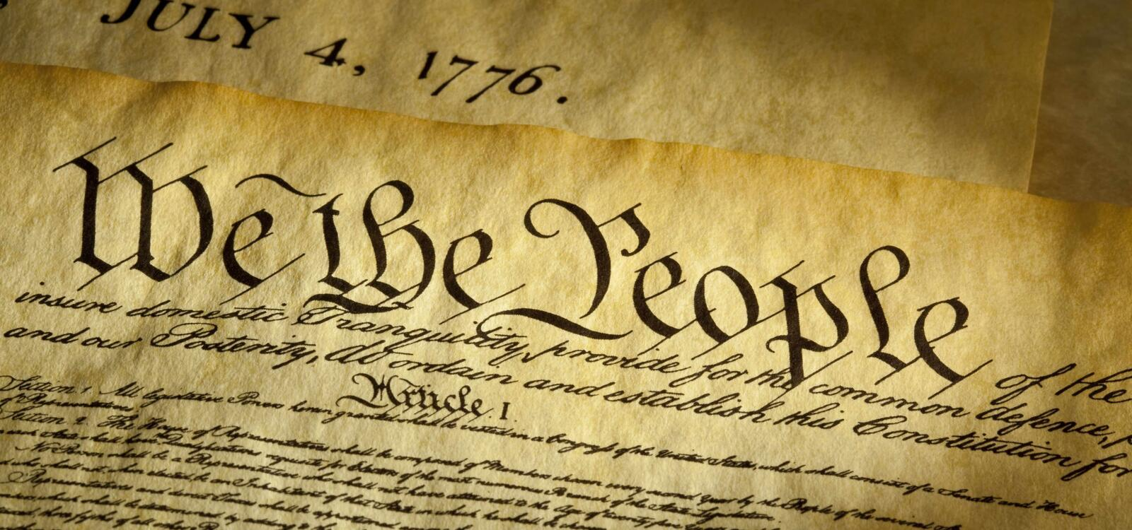 """Pages of the constitution sit on top of each other and showcase the date and the beginning words of """"We the People"""""""