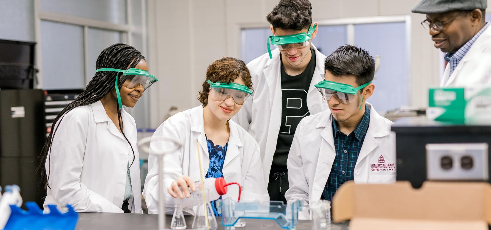 with help from their professor, three students, dressed in white lab coats and goggles, sit around and another student conduct an experiment.