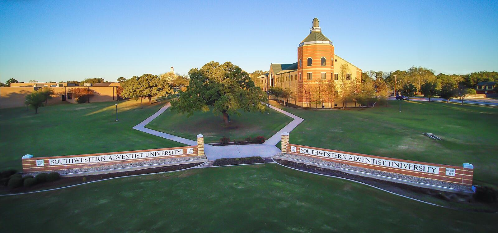 """Birdseye view of the university, showcasing the Pechero building and two matching brick signs that read """" Southwestern Adventist University"""""""