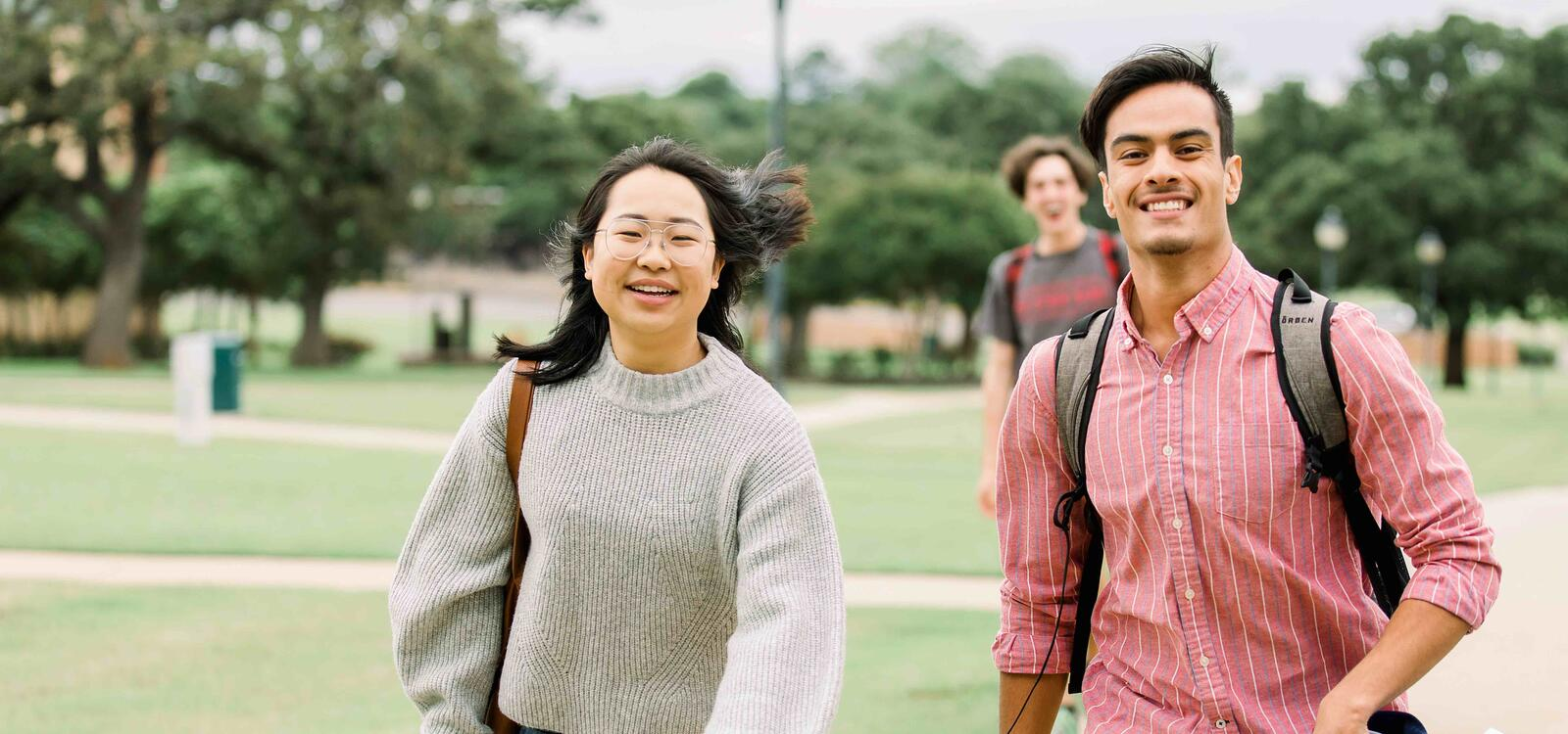 Two students walking across campus together as they talk and smile.
