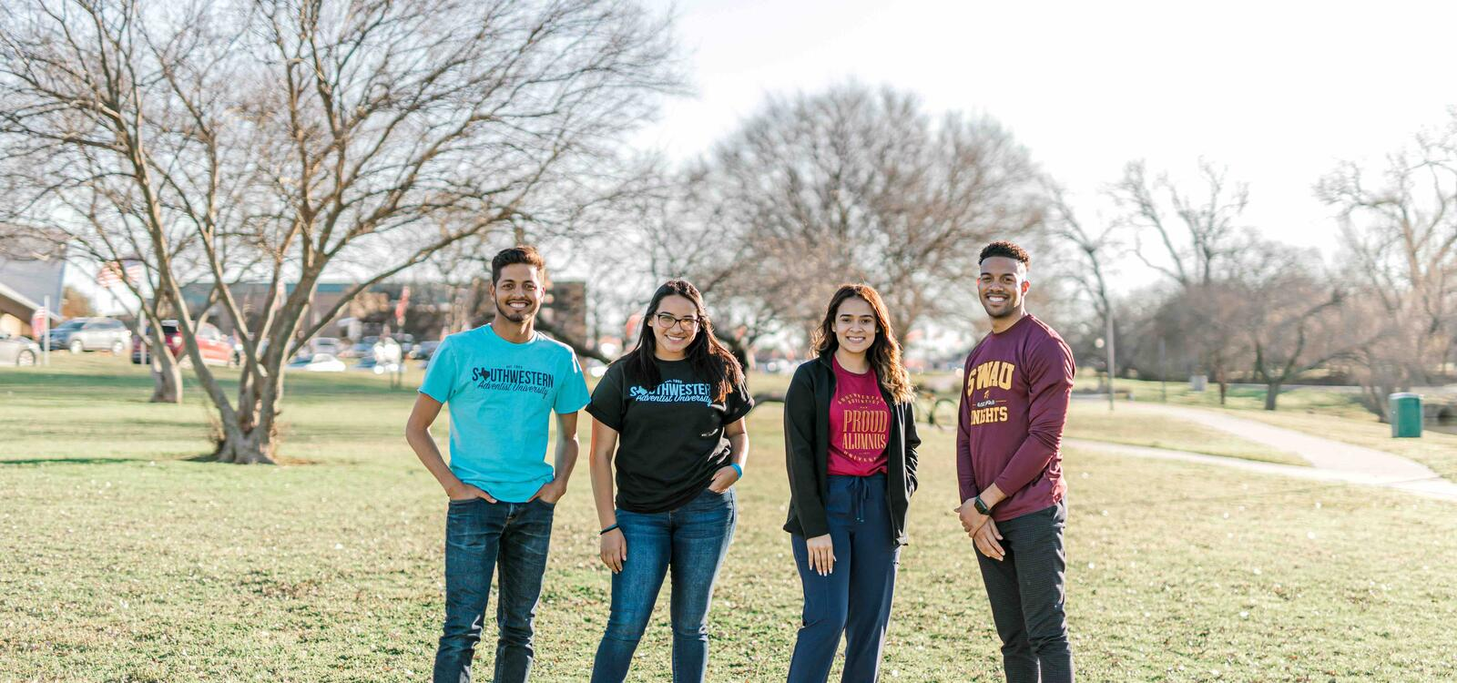 Four students of different ethnicities standing next to each other and smiling