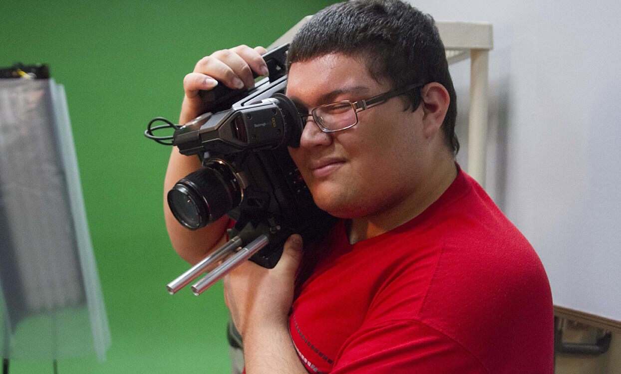 A young man squints one eye as he uses the other to look through the lense of a video camera