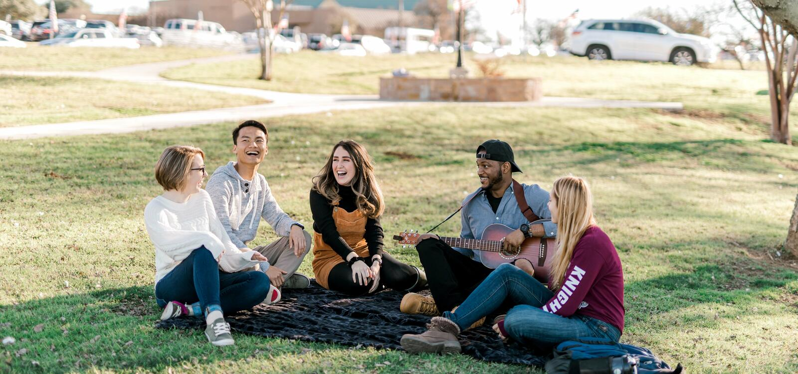 Five students sit under a tree on a blanket laughing and singing as one studentplays the guitar