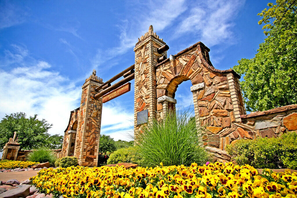 From a lower angle, the Mizpah gate, built of variety of bricks, stands tall in front of blue skys and green trees