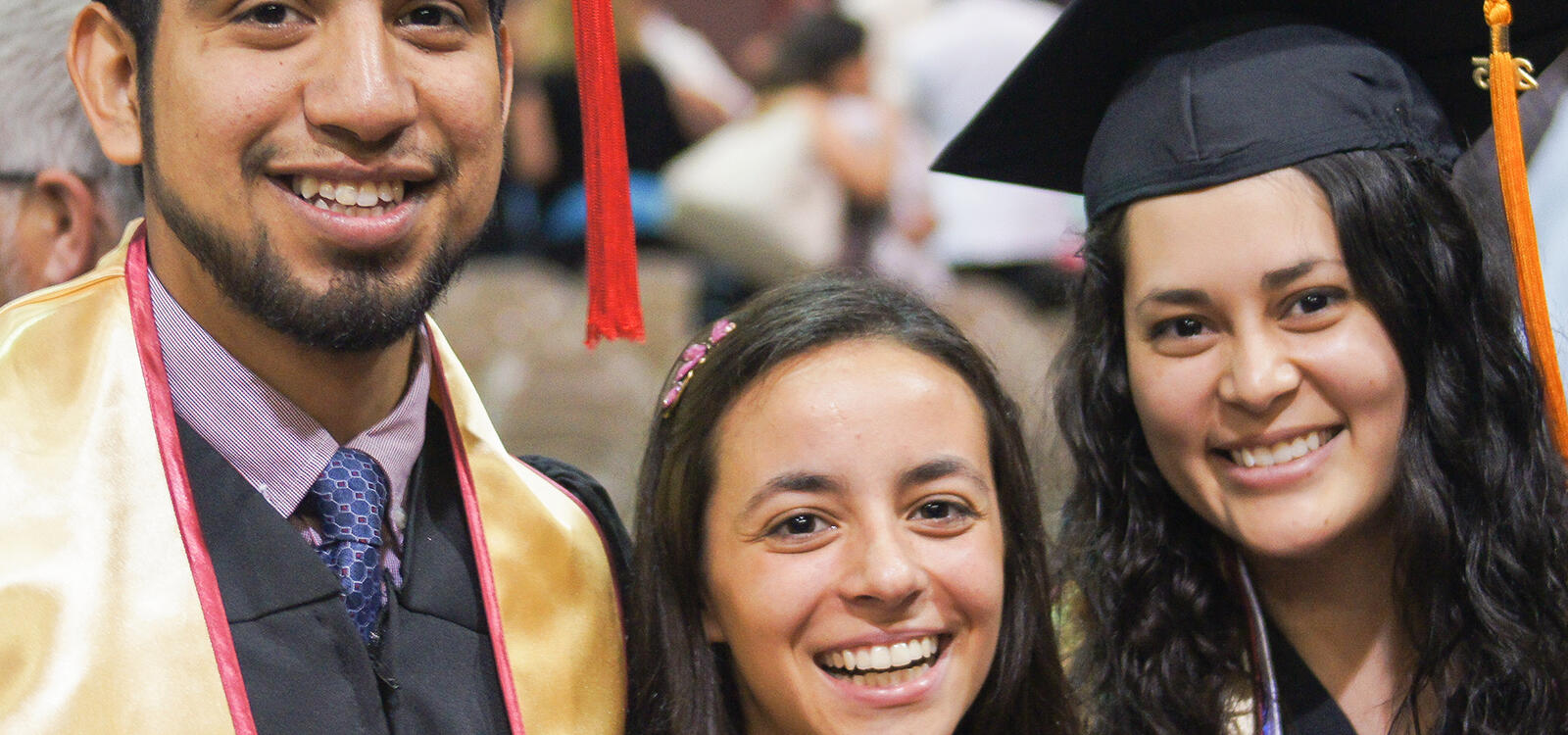 Two graduating students smiling with their peer