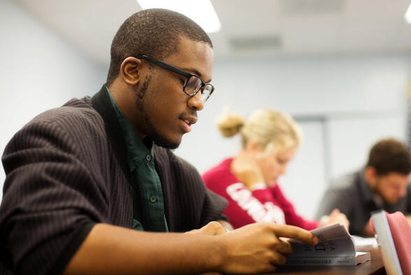 Wearing a forest green button-up and a jacket, a student looks down as he reads a book. In the background, his peers can be seen reading.