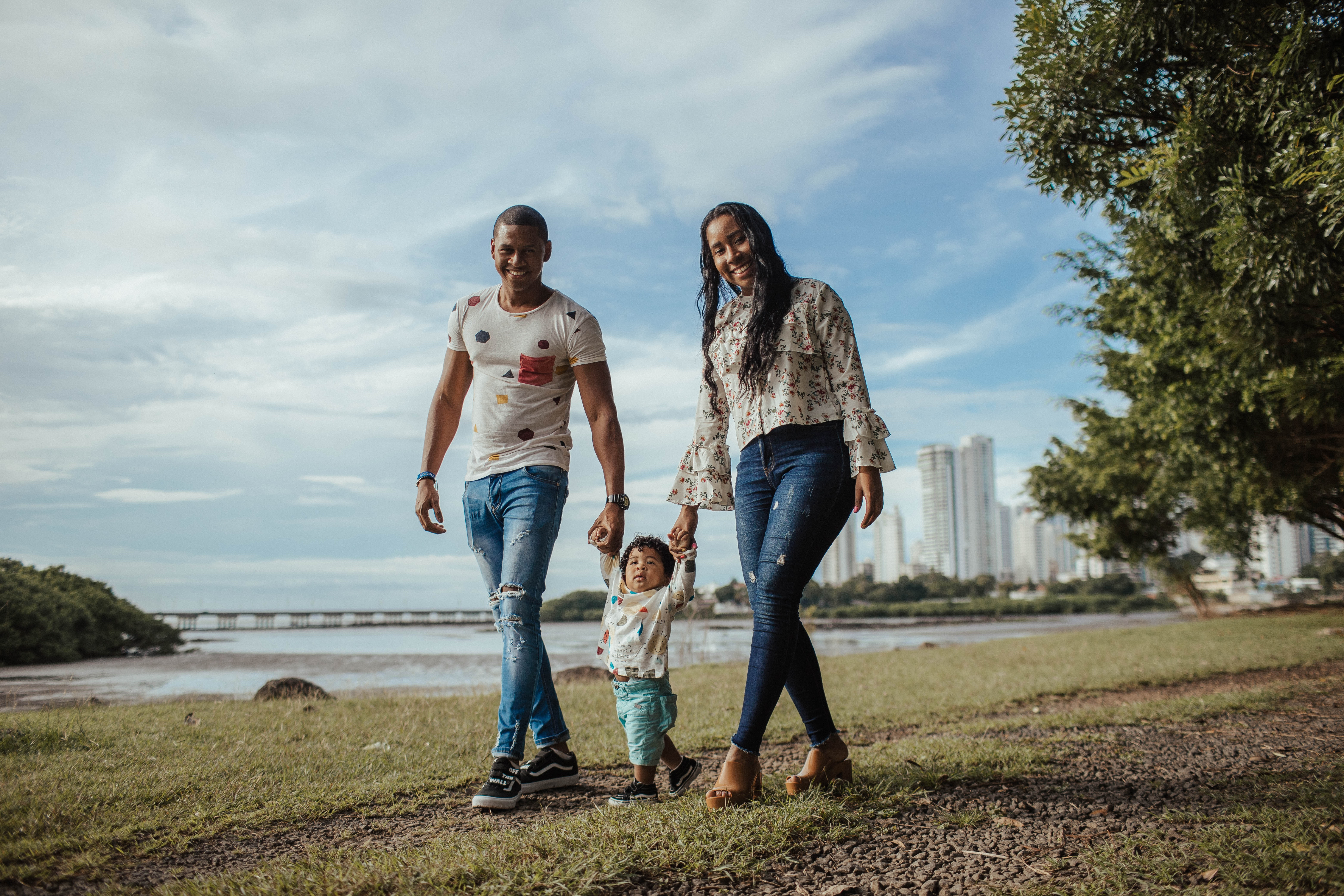 Two young parents smile as they walk together on either side of their child, holding his hands